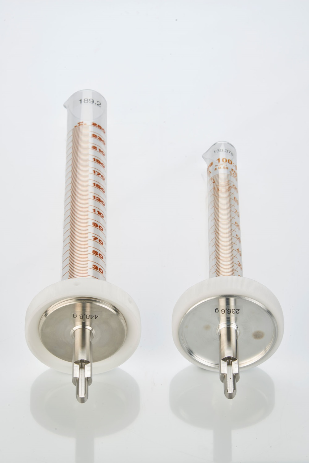Standard 250ml and support (left) and the smaller 100ml cylinder and support (right)