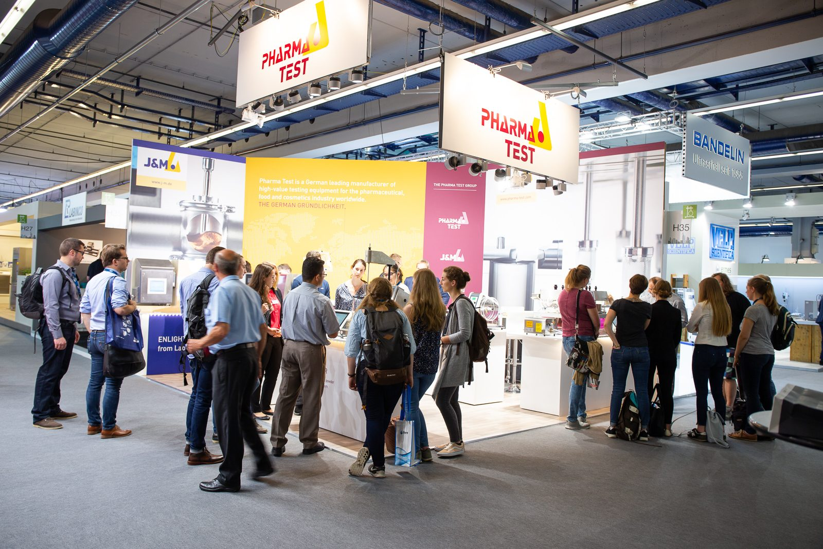 A large group of students visiting the PHARMA TEST GROUP booth...